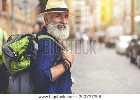 I like traveling. Portrait of happy old man walking in city and smiling. He is carrying rucksack. Copy space in right side