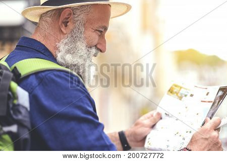 Happy old man is looking at map of town with excitement. He is standing in profile and laughing