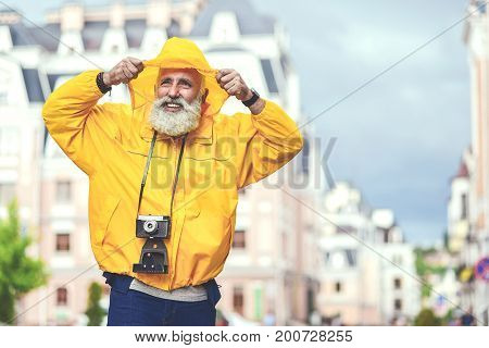 Portrait of happy old man enjoying walk in city. He is wearing yellow hood of windbreaker on his head and smiling. Traveler is carrying retro photo camera. Copy space
