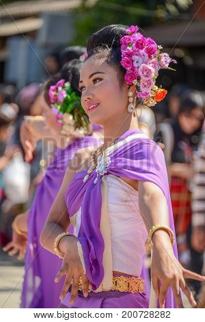 CHIANGMAI THAILAND - JANUARY 25 2015: Indigenous women with traditional purple costume dancing in traditional style in parade of 22nd Traditional Skirt Fabric and The Indigenous Product and Culture Festival in Mae Chaem Chiangmai Thailand
