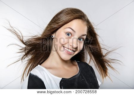 Funny Girl With Windy Hair. The Girl Smiles And Opens Her Eyes Wide