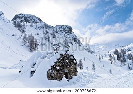 Mountain hut made of stones - shelter for mountaneers from the snow storm in winter, mountain Vogel, slovenian Alps, Slovenia