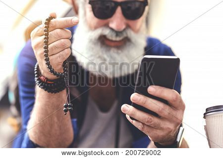 Cheerful old man is calming down himself while counting beads. He is using smartphone and smiling. Focus on chaplet in his hand