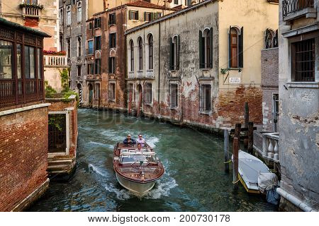 Venice Italy - May 17, 2017: The motor boat with tourists sails along the canal in Venice. Motor boats are the main transport in Venice.