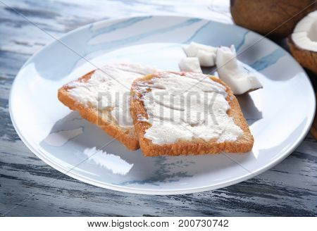 Delicious toasts with coconut oil in plate on table, closeup