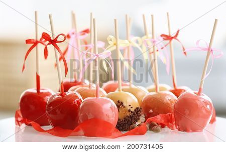 Delicious candy apples on table against blurred background
