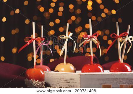 Wooden tray with delicious candy apples on blurred background