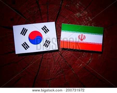 Iranian Flag With South Korean Flag On A Tree Stump Isolated