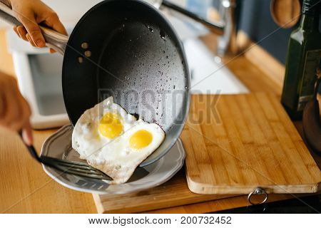 Two fried eggs in a pan with olive oil. Girl's hand holding a frying pan with scrambled eggs.