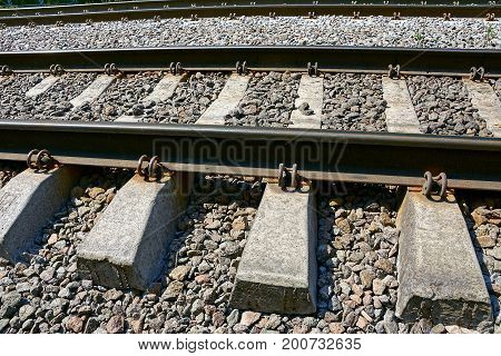 Steel rails and concrete sleepers in the stones on the railway