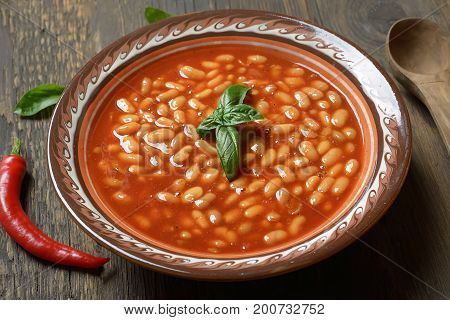 Beans in tomato in a dish on a wooden background