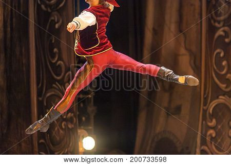 choreography, playing, staging concept. young male ballet dancer, depicted in the photo in midflight, wearing elegant bright costume for performance, red satin vest to match sweatpants