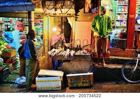 2014 March 1 Kathmandu streets daily life people selling fresh fish on night street market Kathmandu Nepal.