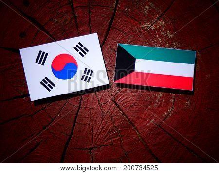 Kuwaiti Flag With South Korean Flag On A Tree Stump Isolated