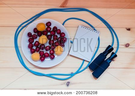 Fruits notebook and skipping rope on wooden background
