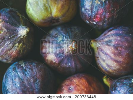 Close-up of fresh ripe purple figs, top view. Food texture and background. Organic fruit, local produce, farming, healthy food concepts