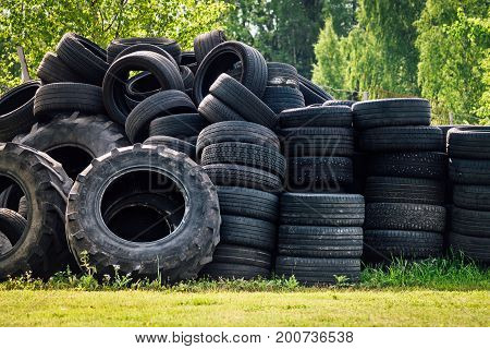 A large stack of used up vehicle tyres stapled in rows