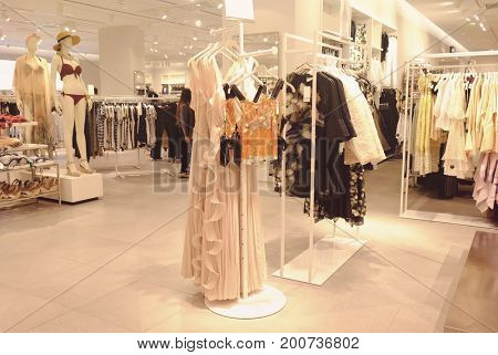 Different female clothes in modern shop
