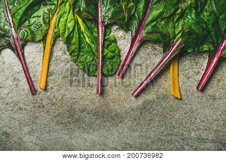 Flat-lay of fresh colorful leaves of swiss chard over concrete stone background, copy space, top view. Food frame. Clean eating, vegan, vegetarian, alcaline diet, organic, healthy cooking concept