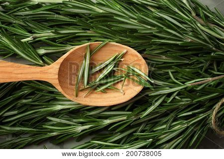 Wooden spoon on fresh rosemary