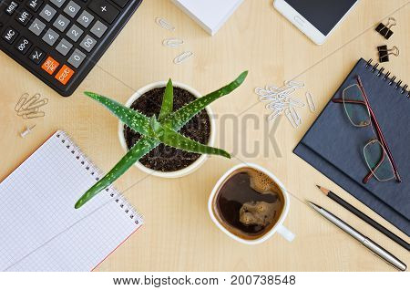 Top view office desk with notepads phone paper for notes calculator glasses and cup for coffee.