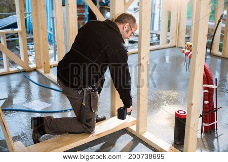Carpenter Drilling Wood While Kneeling At Construction Site