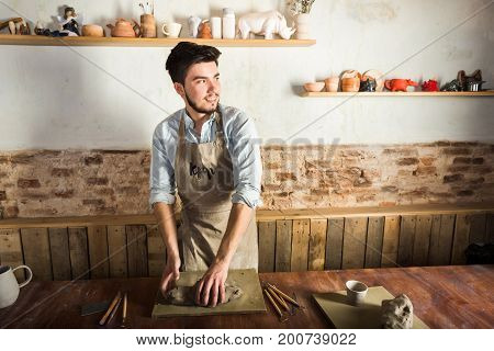 potter, workshop, ceramics art concept - standing young smiling brunette man with hands knead fireclay, male dressed in an apron, a ceramist with raw materials on wooden table with sculpting tools set