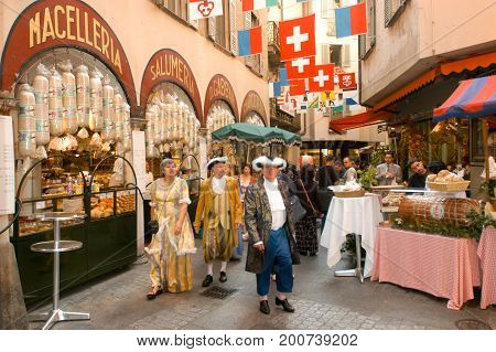 Lugano Switzerland - 27 September 2002: People in traditional costumes walking at the pedestrian street in the center of Lugano on the italian part of Switzerland