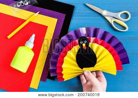 Making souvenir for Thanksgiving: turkey made of paper. Original children's art project. DIY concept. Step-by-step photo instructions. Step 8. Child glues together all elements of souvenir turkey