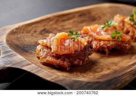 hash browns and salmon on wooden plate