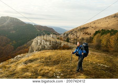 Redhead bearded hiker going up the trail path. Backpacker man climbing a mountans with trekking poles. Beautiful autumn scenery