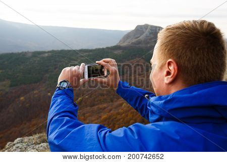 Hiker sitting and taking photo of mountain landscape with mobile phone. Climber man photographing panorama with smartphone on summit.