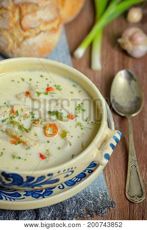 Traditional tripe soup on wooden table, close up