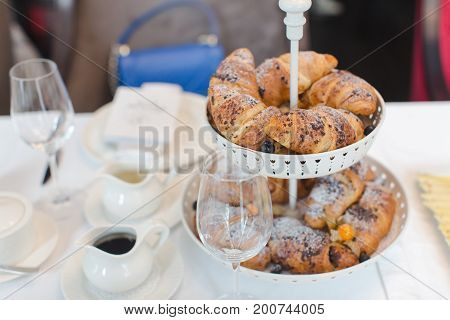 Table served for meal with stand of freshly baked buns.