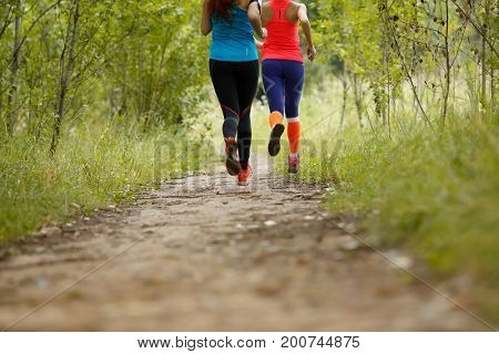 Two running athletes in park
