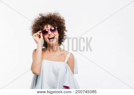 Young attractive woman in sunglasses looking at camera and laughing isolated over white background