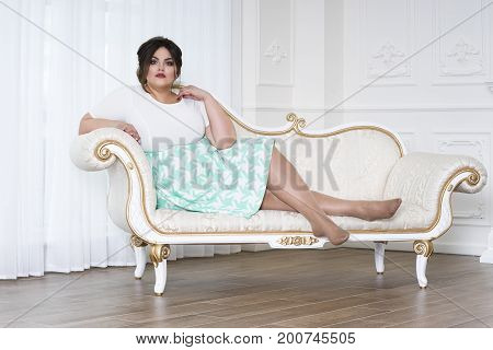 Plus size fashion model fat woman on luxury interior overweight female body professional make-up and hairstyle