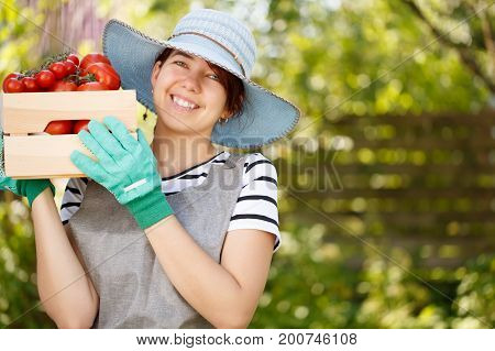 Portrait of brunette in hat with box of tomato in garden