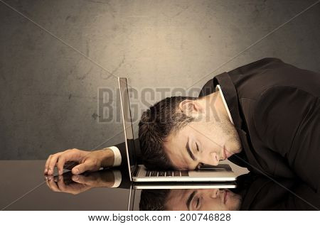 A sad and depressed office worker resting his head on a keyboard while shouting in front of a grey grungy wall background