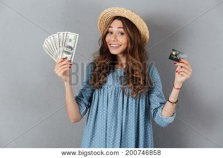 Image of amazing young pretty woman standing over grey wall wearing hat holding money and credit card.