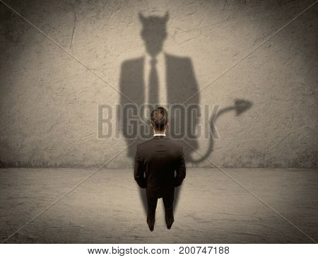 An experienced tricky businessman in suit looking at his devil desguise shadow reflected on the wall concept