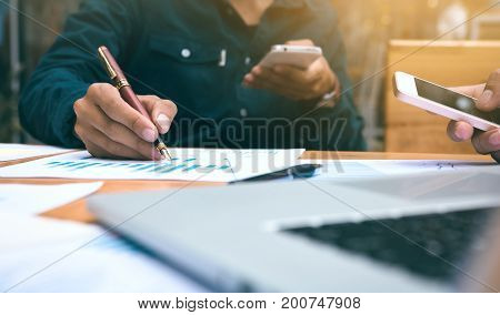 Businessman writing or pointing summary report chart and using smart phone looking data.