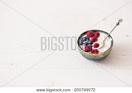 Top view on small bowl with organic yogurt with blueberries and raspberries on white wooden background. Girl having healthy breakfast at home. Healthy eating snack.