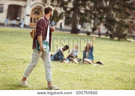 Student With Books Looking At Classmates