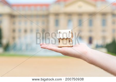 Man Hand Holding A Wooden Model House Over The Blur Building