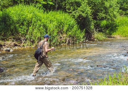 Man Fishing On A Mountain River With A Ultralight Spinning Using Fishing Wobblers. He Got His Hook H