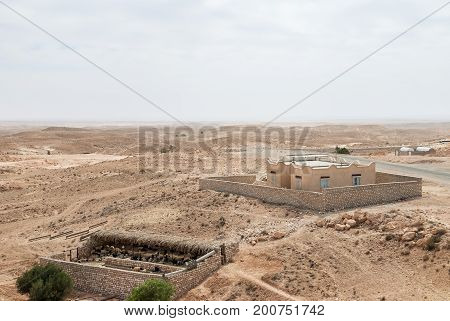 Sheepfold and a building in the middle of an arid desert with a horizon line