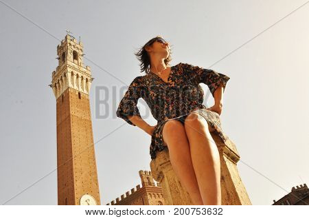 Bottom view of a woman sitting on the Piazza del Campo in Siena against the Torre del Mangia tower and the sky