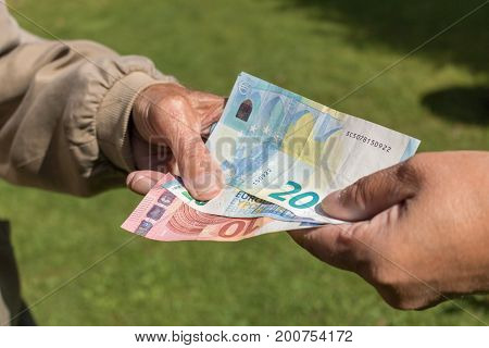 Senior man's hands holding Euro banknote. pensioners concept.