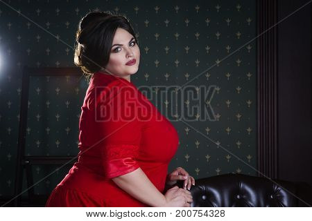 Plus size fashion model in red evening dress fat woman on luxury interior professional make-up and hairstyle